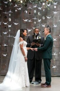 03 a wedding backdrop made of paper cranes and couples photos plus greenery on top 1